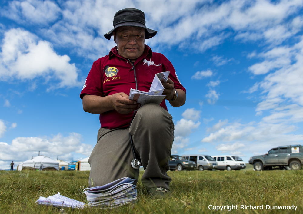 Mongolian Vet Nyamdavaa checks the veterinary cards at Horse Station 12. Race Day 5 10th August 2014