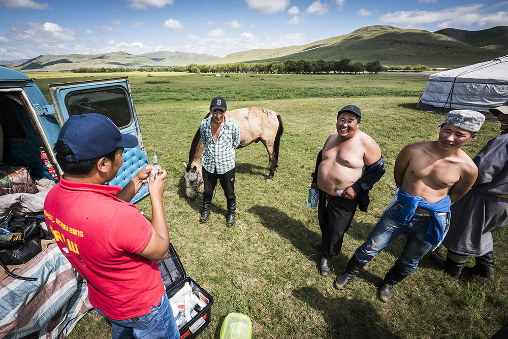 Mongolian vet Erdene Munkh prepares to treat William Comiskey's horse at Urtuu 9. He found it to be slightly lame and brought it back to the station. The owner is bare- chested at the centre