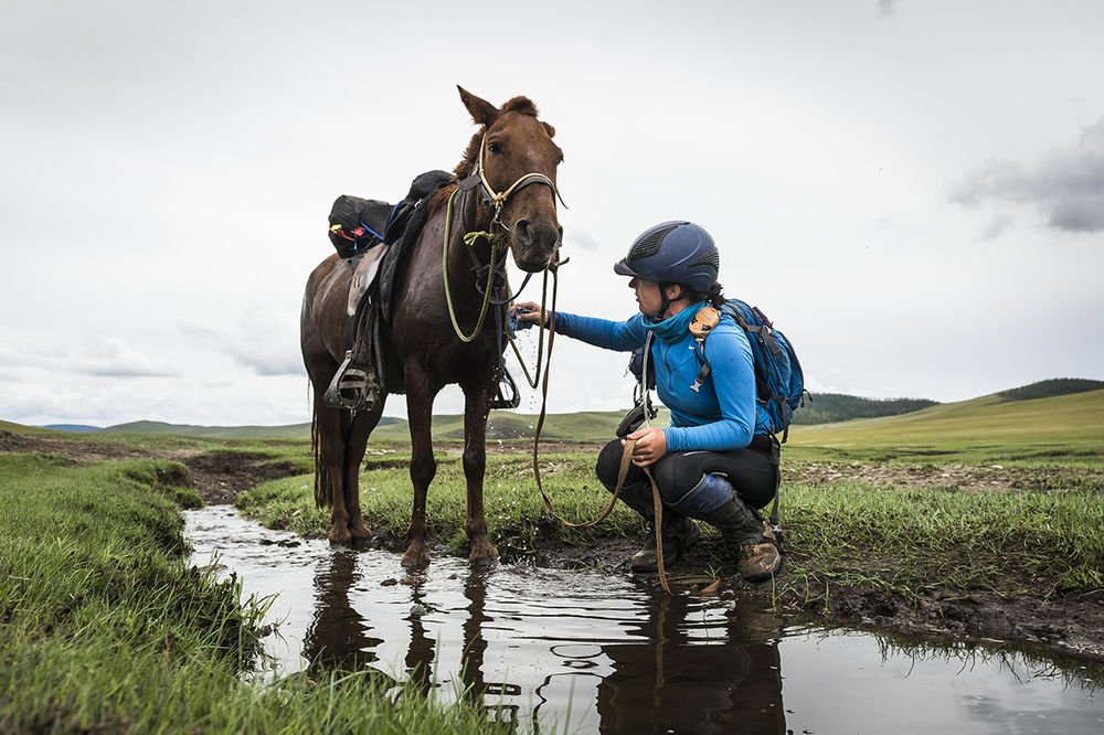 Camille Champagne Bargenquast washes her horse down with cold water on her way into Urtuu 16  Photo by Richard Dunwoody for Mongol Derby