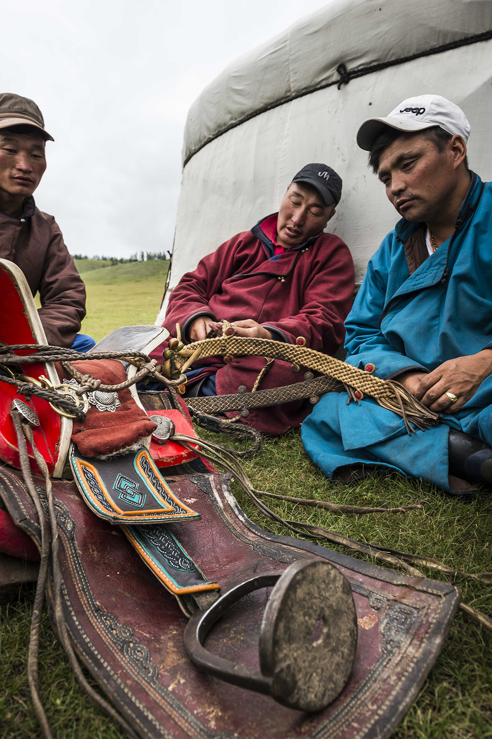 Herders discuss the decorative girths on a Mongolian saddle, Urtuu 20  Photo by Richard Dunwoody for Mongol Derby