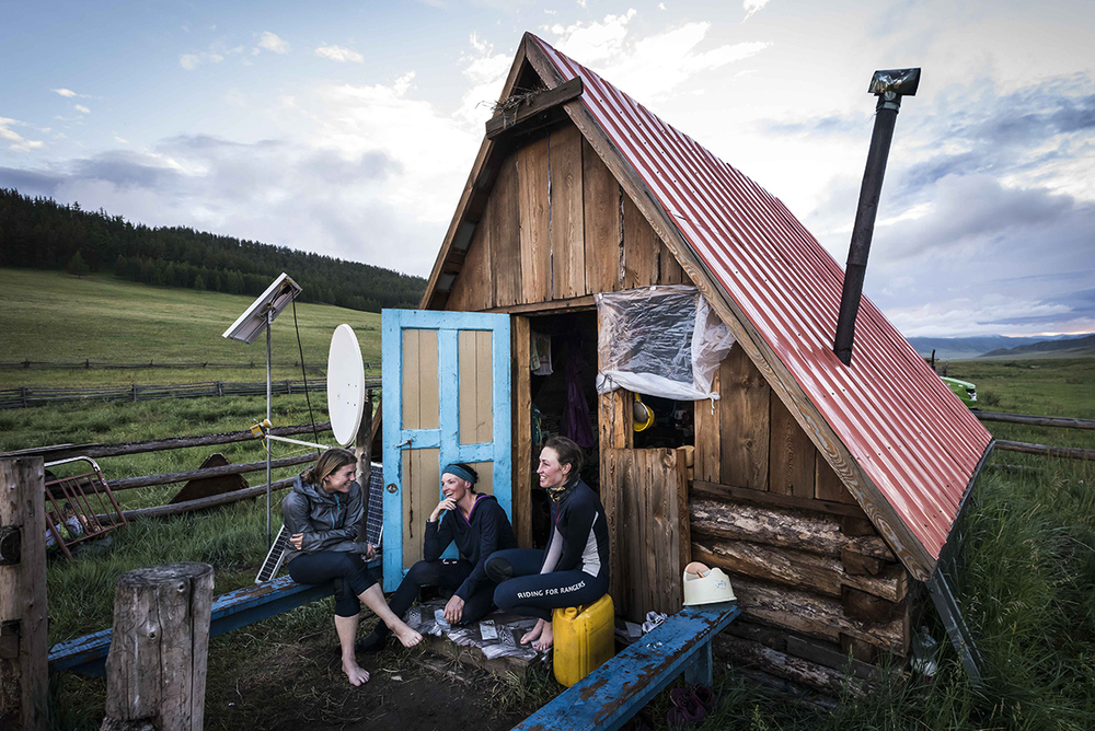 Venetia Philipa, Marcia Hefker-Miles and Tatiana Mountbatten appear in good spirits having found a log cabin equipped with wood burner and satellite tv to bed down for the night between U22 and U23  Photo by Richard Dunwoody for Mongol Derby