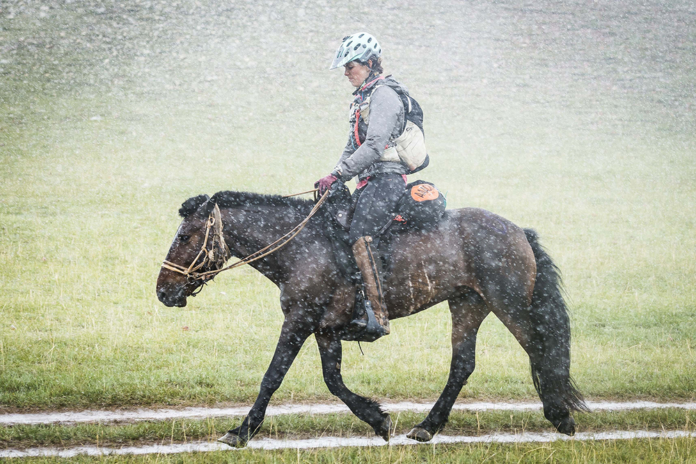 Courtney Kizer, a close fourth, riding into Urtuu 25 in a torrential rain shower.   Photo by Richard Dunwoody for Mongol Derby