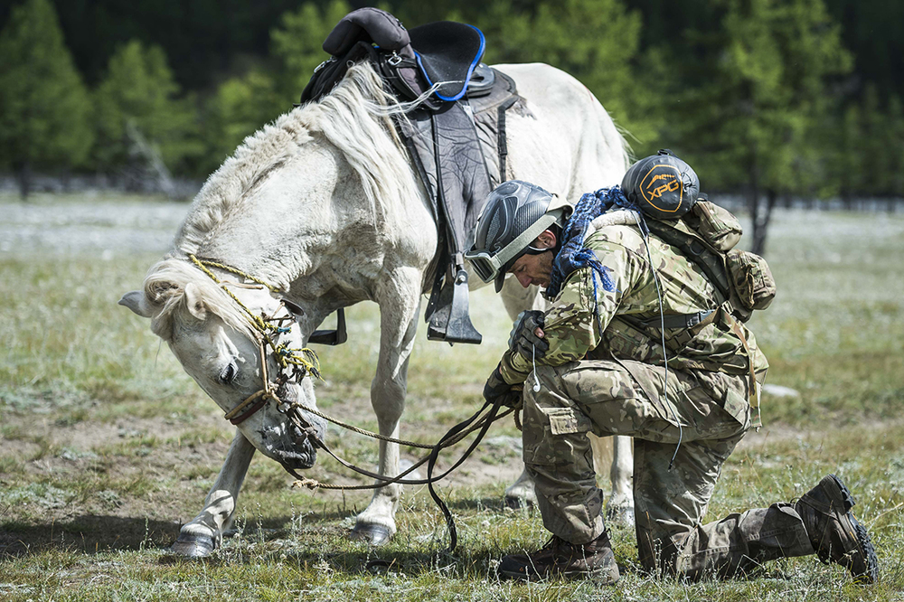 Tim Finley says a prayer to his military colleagues who have taken their own lives since returning from service in Afghanistan and Iraq. He named a horse on every leg of the race after one of his colleagues that have passed away.