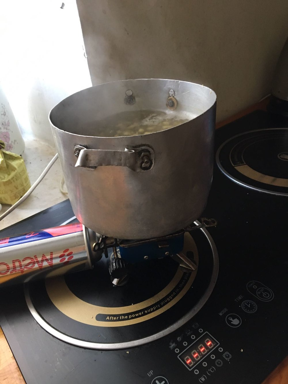 Ginger and sugar on the boil. Why yes, that is a camp stove on top of an induction stove.