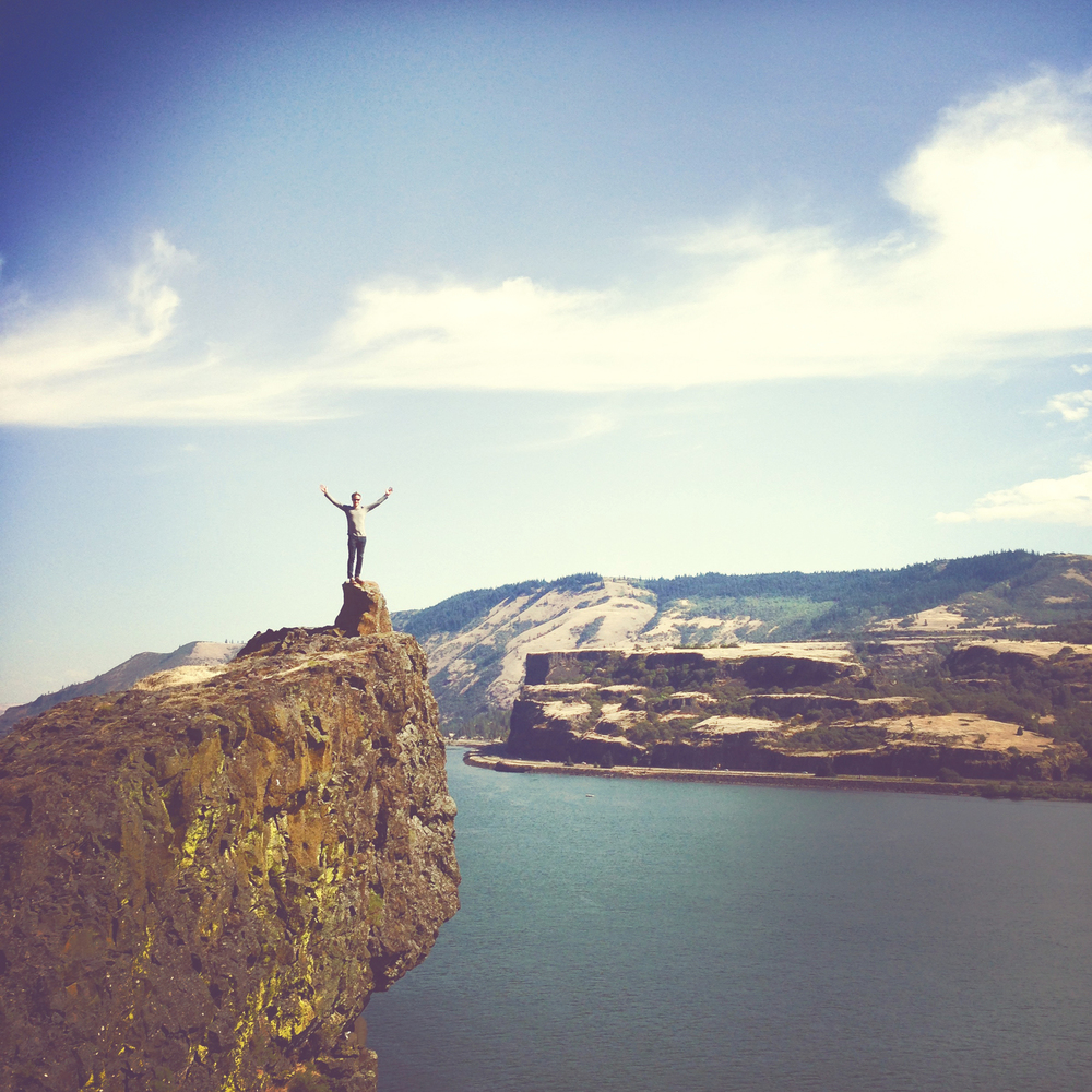 Paragliding pilot standing on cliff near Portland, OR.