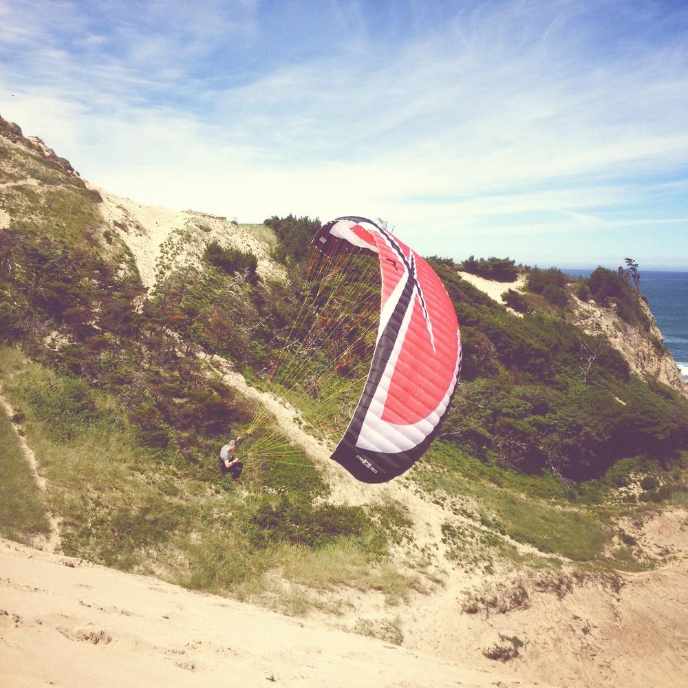 Pilot paragliding from dune in Oceanside, Oregon coast