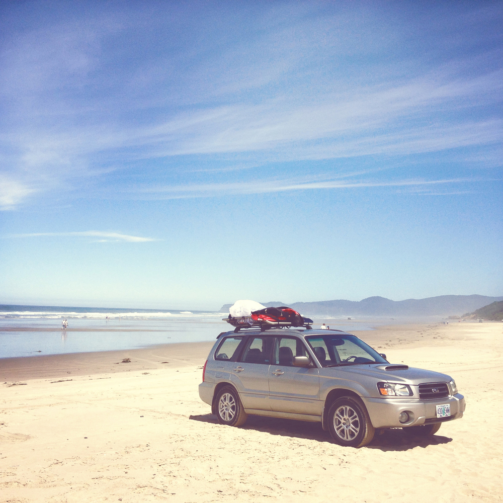 Car on Oregon beach full of gear for paragliding lessons.