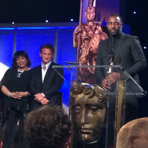 Zindzi Mandela and Sean Penn look on as Idris Elba makes his acceptance speech at BAFTA Los Angeles Britannia Awards
