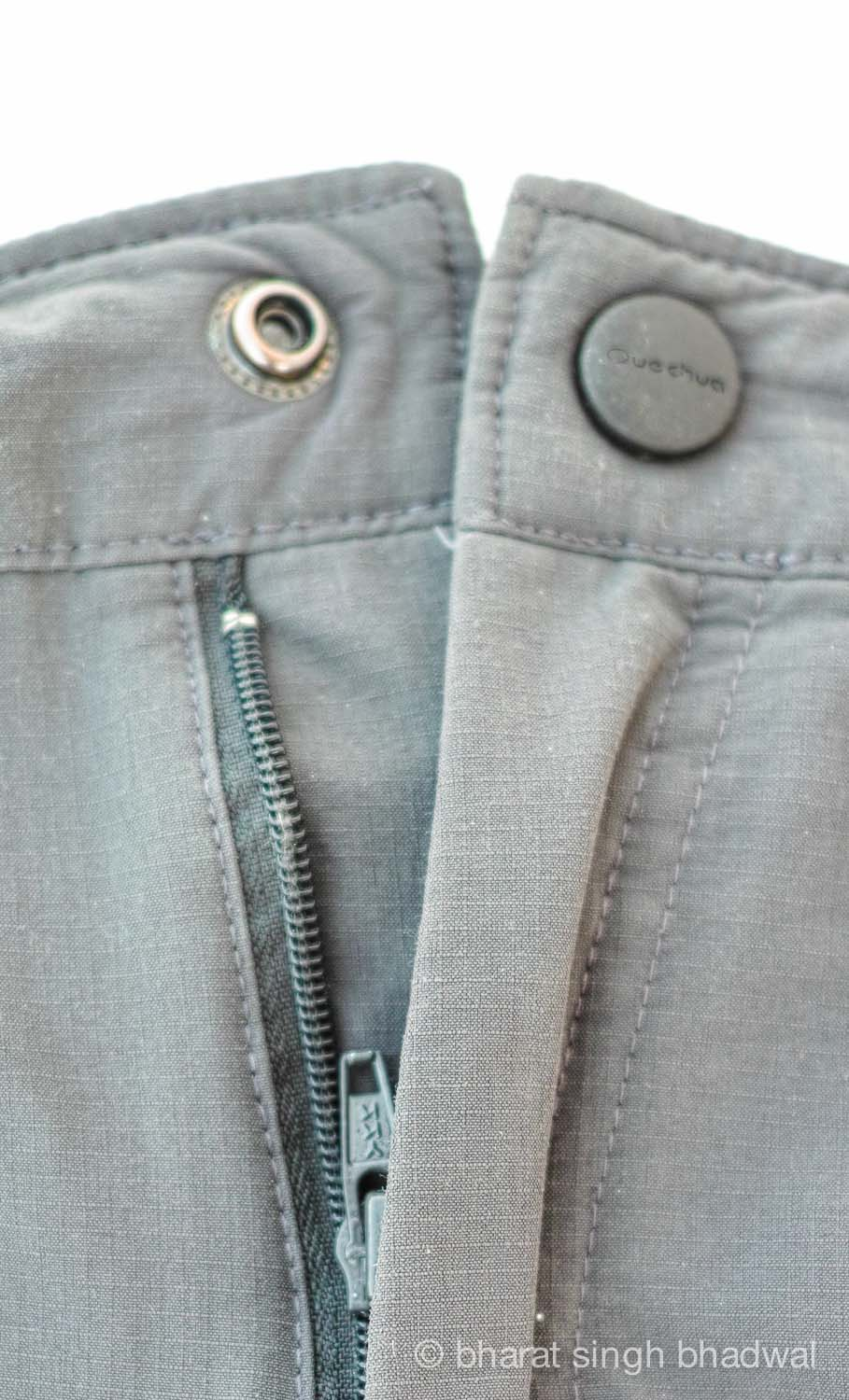Front snap with subtle branding and YKK zipper. The ripstop fabric (small squares) is evident