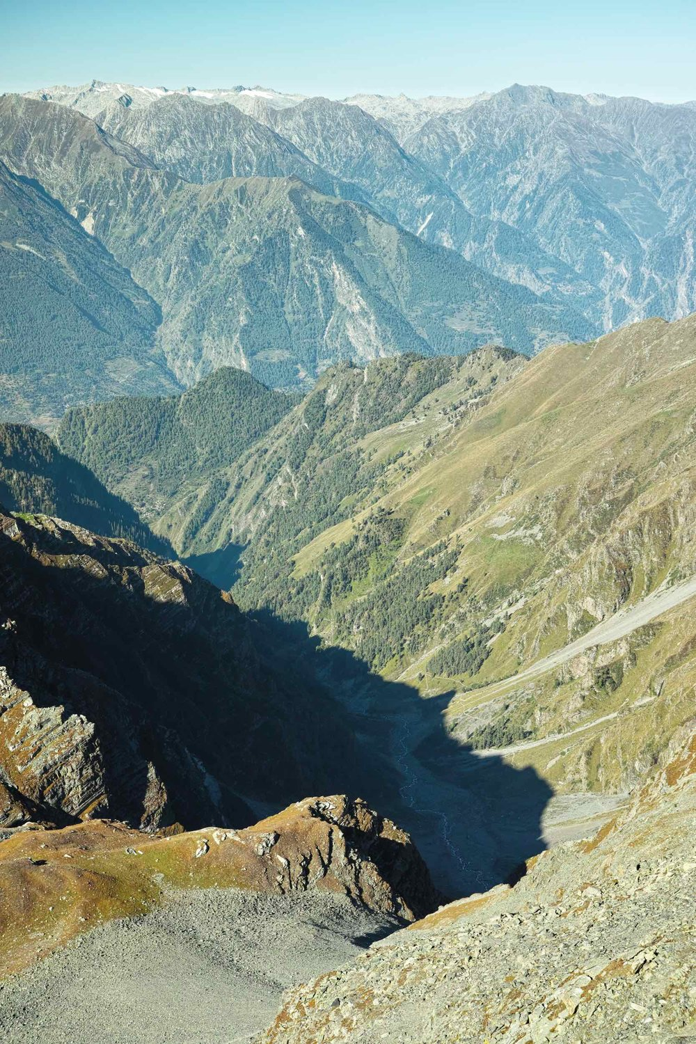 "The view south from Kalah Pass. Zoom in to see the trail towards ""Tiyari"" village along the mountain stream. The white capped mountains in the background are the Dhauladhars."