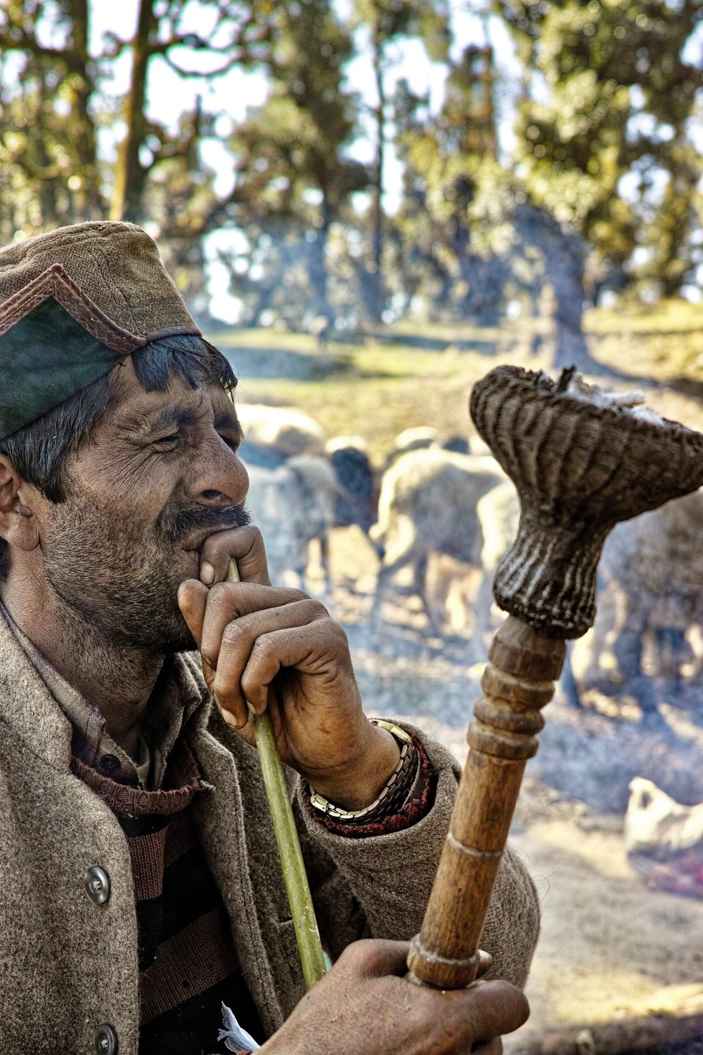 A Gaddis Smoking a Hookah - Nomadic shepherds in the Indian Himalayas.  Mainly living in the North Indian states of Himachal, Uttarakhand and Jammu & Kashmir. During their oscillatory migration, Gaddis carry some light utensils, maize flour, salt and some other basic essentials in a Khalru (sheep skin bag). This Khalru is often loaded like a backpack by a Gaddi. In addition to the Khalru, he always carries his Hookah and tobacco in a leather pouch. Very often, a Gaddi will carry a new born lamb in his Chola (wooden coat). Since they do not carry tents, Gaddis prefer sleeping in the open. When the weather turns inclement, they seek shelter under natural rock projections or trees and use their blankets made from goat hair. Rough but extremely warm. Gaddis are extremely fond of their dogs and these dogs are very territorial and are on herd guard duty at night.