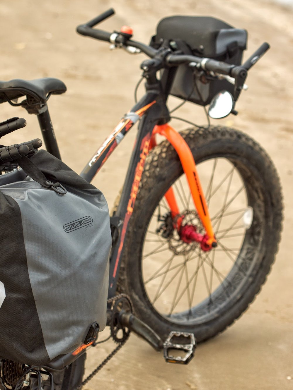Fully loaded bicycle with handlebar bag and rear panniers.