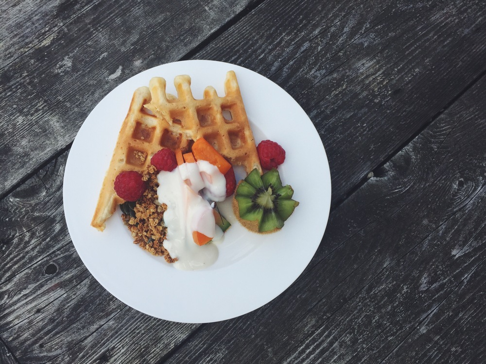 Homemade oat waffles with homemade maple syrup granola, chopped fruit and almond yoghurt