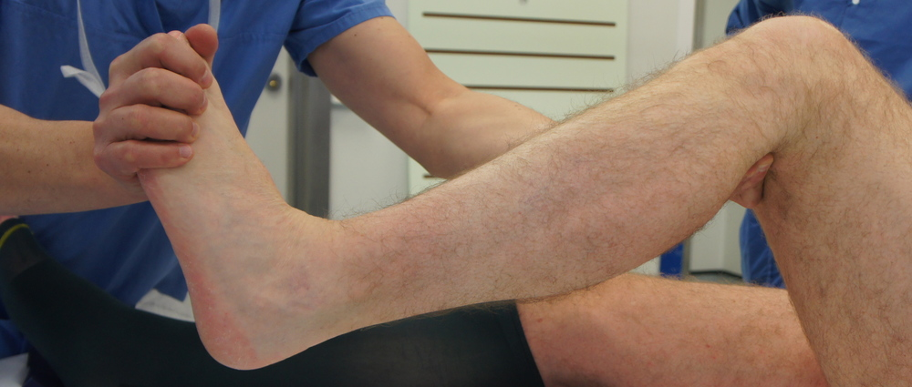 Clinical photograph, with the knee bent, the calf muscle is relaxed and ankle bends back further, this means that the Gastroc must be the tight muscle.