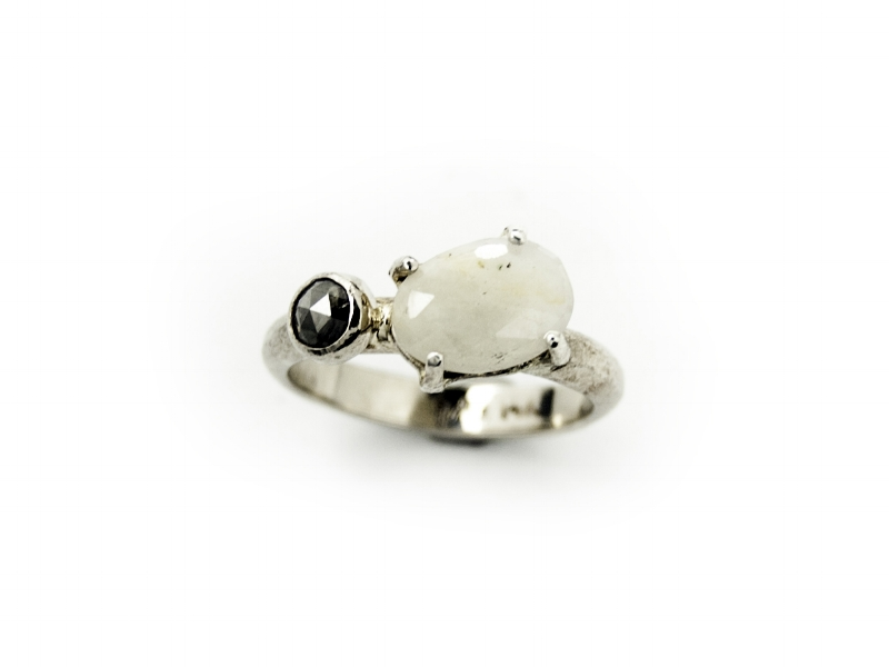 A white gold pebble band featuring a rose cut white sapphire and grey natural diamond.