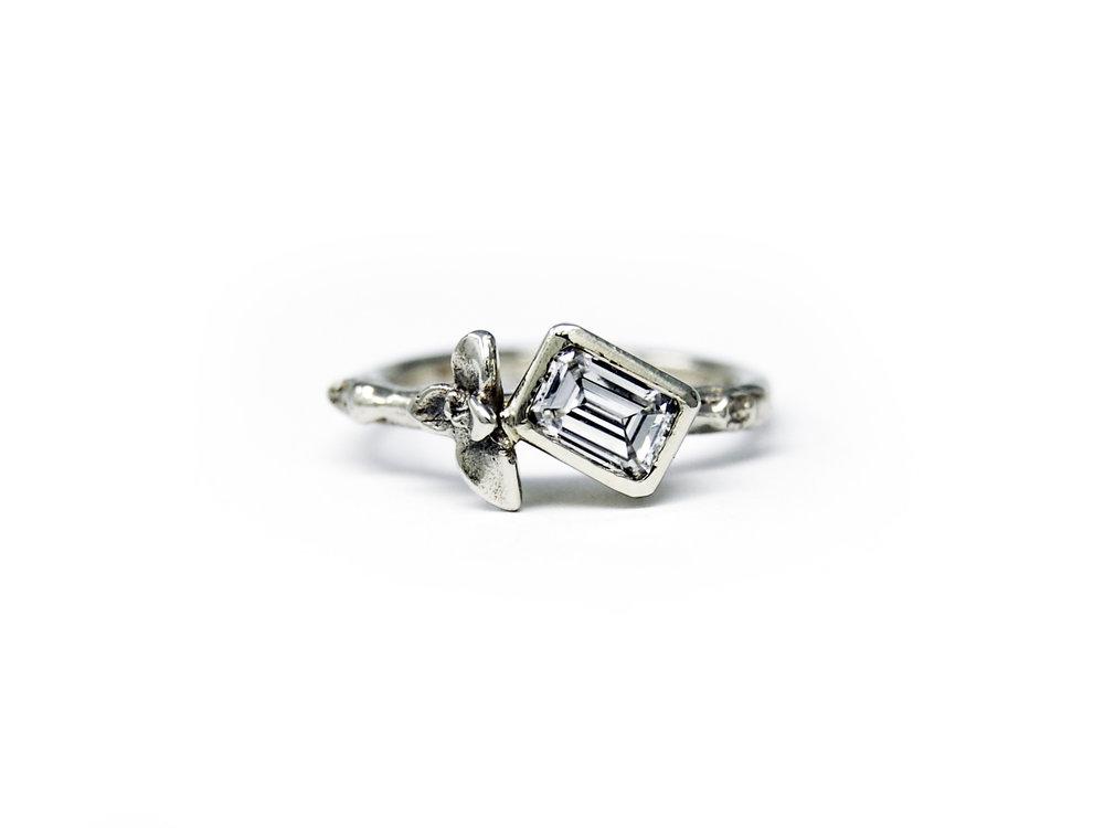 A custom 14kt white gold twig + succulent ring featuring our clients gorgeous emerald cut heirloom diamond