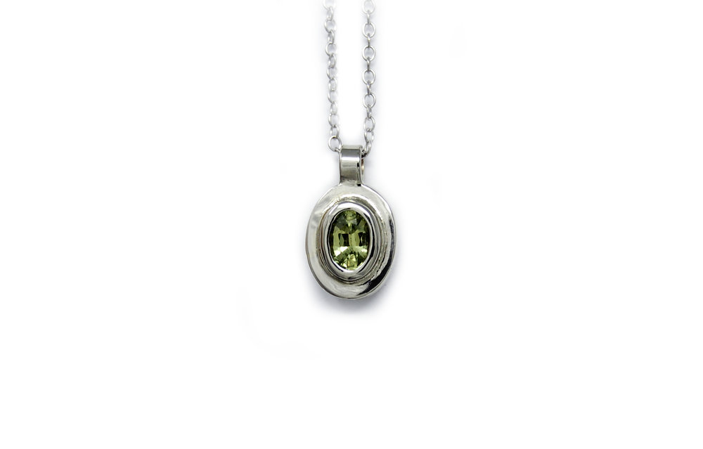 An 18kt white gold pendant featuring a green Parti Sapphire