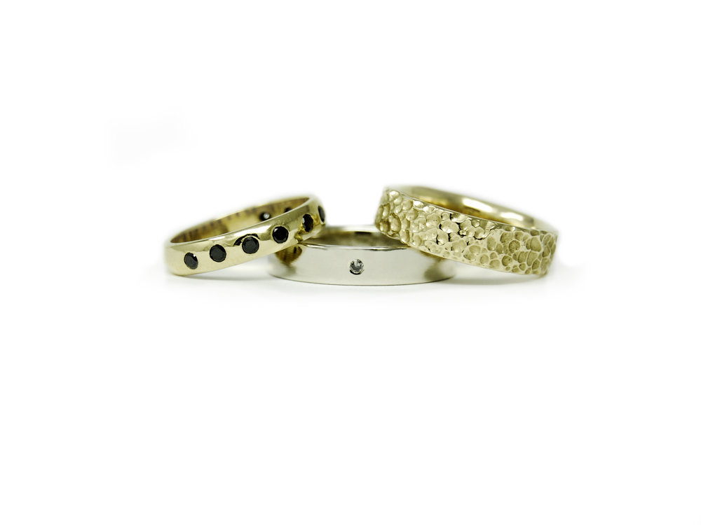 Two yellow gold wedding bands for the bride, featuring our signature CRATER texture and black diamonds. A white gold wedding band for the groom with a small salt + pepper flush set diamond.