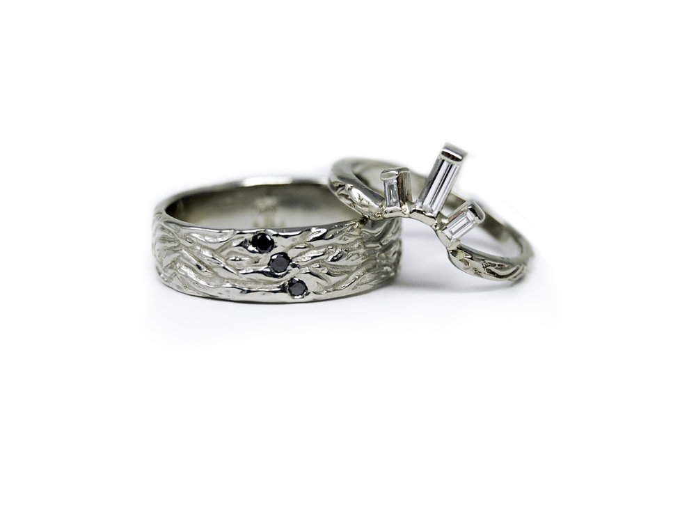 His and hers wedding bands in recycled white gold in a custom texture with prong set baguette diamonds.