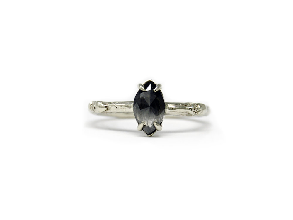 A recycled white gold engagement ring featuring a marquise cut salt and pepper diamond.