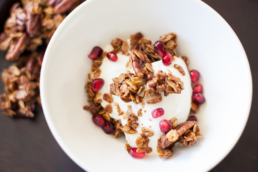 gingerbread spiced granola with pecans over yogurt and a sprinkle of pomegranate seeds