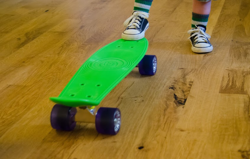 A pair of little feet play with a skateboard on a solid character oregon white oak floor.