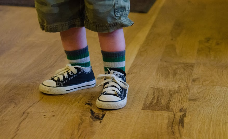 A toddler - with the cutest pair of Chuck Taylor All stars I've ever seen - is standing on a character Oregon White Oak floor.