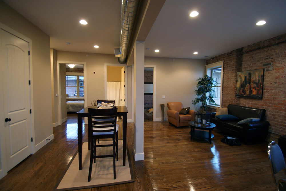 refinished hardwood floors, exposed brick wall and ductwork with large windows for natural light.jpg