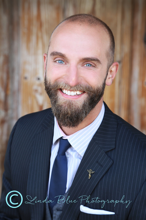 Well groomed beard and neat haircut, dark suit with subtle pinstripe, nice complementing shirt and tie (blue brings out his blue eyes), Background is outdoors adds a bit of casual feel to the photo.