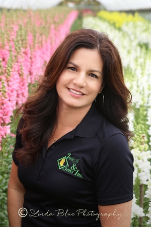 Simple makeup, natural hairstyle, solid dark shirt with her business logo, location is  highlighting her flower business.