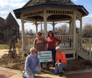 Jackson County Master Gardener Volunteers pose in front of the Grass Lake Depot Project.