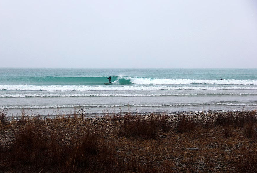 Great Lakes surfer Jacob Kaiser enjoying an ice-cold right point; photo by Brian Tanis