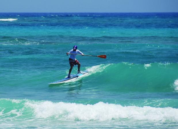 Sup surfing a green wave at Glover's Reef, Slick Rock resort in Belize