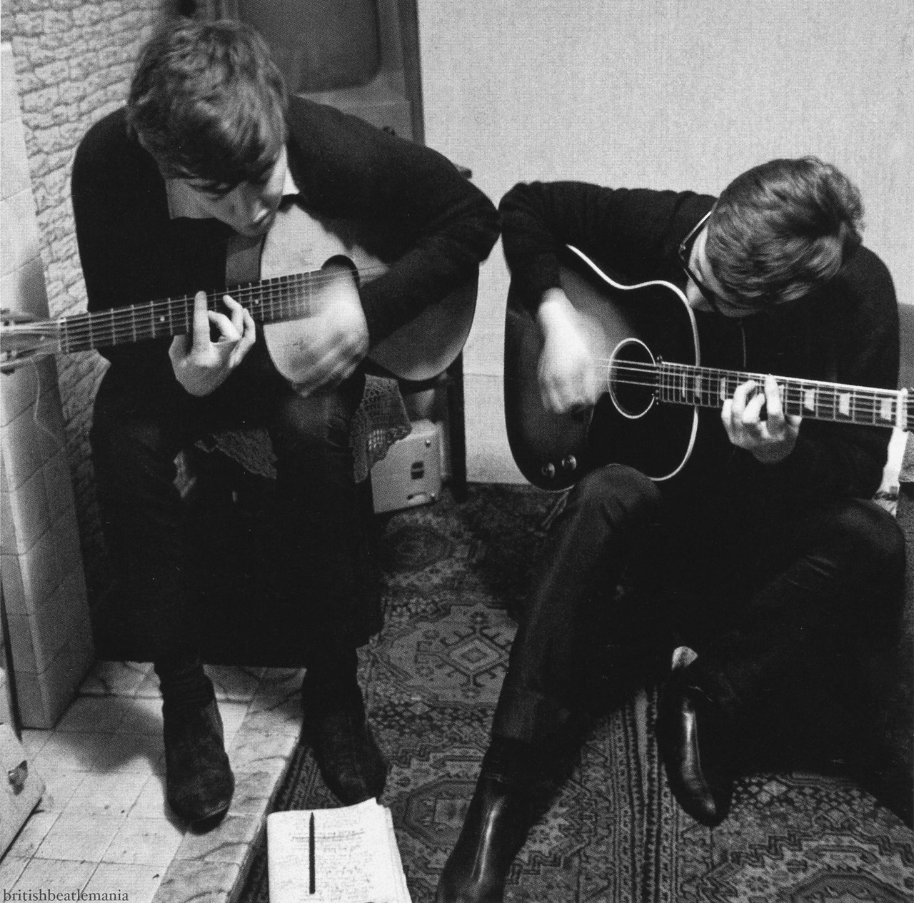 "austinkleon: Paul McCartney and John Lennon writing ""I Saw Her Standing There,"" 1962 I looked this photo up after reading about it in Joshua Shenk's Powers of Two: Finding the Essence of Innovation in Creative Pairs: One late November afternoon in 1962, John Lennon and Paul McCartney got together to write at Paul's house at 20 Forthlin Road in Liverpool. Their ritual was to come around in the afternoon, just the two of them, when Paul's dad was at work. They would go to the small front room overlooking Jim McCartney's patch of garden and sit opposite each other. ""Like mirrors,"" Paul said. John sat on a chair pulled in from the dining room. He had his Jumbo Gibson acoustic-electric with a sunburst finish. Paul sat on a little table in front of the telly with his foot on the hearth of the coal fireplace. He played a Spanish-style guitar with nylon strings, strung in reverse for a lefty. In a photography shot by Paul's brother, Michael, they're both looking down at a notebook on the floor, filled with lyrics… …Years later, Paul told his brother that he loved his photo of the ""I Saw Her Standing There"" writing session because it captured how it really was—""the Rodgers and Hammerstein of pop at work."" Writing ""eyeball to eyeball,"" as John said, they weren't just frontmen for a rock group; they were composers working in concert. There's a Lennon/McCartney excerpt of the book over at the Atlantic. Photo credit: Mike McCartney, image via britishbeatlemania Filed under: The Beatles"