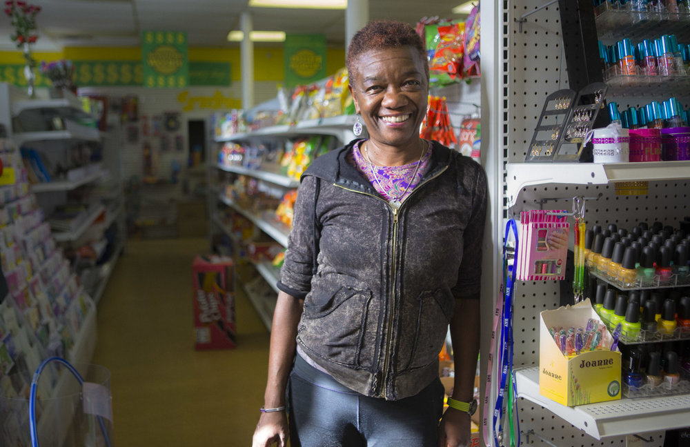 "KATHY, THE SHOPKEEPER   //  Flint, Michigan ""I was for Hillary the first time she ran against Barack… I think she's qualified, first and foremost, and I want to see how a woman would run the country."" The sign outside the Healthy Dollar in Downtown Flint, Michigan says, ""Holla!"" Inside, an array of brightly-colored snacks line the shelves, and a friendly woman called Kathy sits behind the counter. A tall man in a baby blue velour jumpsuit leaves his seat and walks outside. ""Koreans are hilarious,"" she says with a laugh, clapping her hands. A retired reporter for the automotive industry, she's well-traveled woman and reminisces about Seoul, London, Japan. ""I think Barcelona was my favorite. I lived a short walk from the beach, the Mediterranean."" Having graduated high school in 1968, she talks about how involved young people were, politically, back in her day. The conversation glides from Mrs. Clinton's qualifications to the global perception of the US, to the opportunities found in Flint for young people looking to start their own thing. ""Life is interesting,"" she says, ""and for the most part, I still like people."" The door opens. The man in velour returns to continue his visit with Kathy.   Flint, MI: • Population: 98,310. • Per capita income: $14,527. • 56.6% Black, 37.4% white, 3.9% Latino. • Percentage below poverty line: 41.5%."