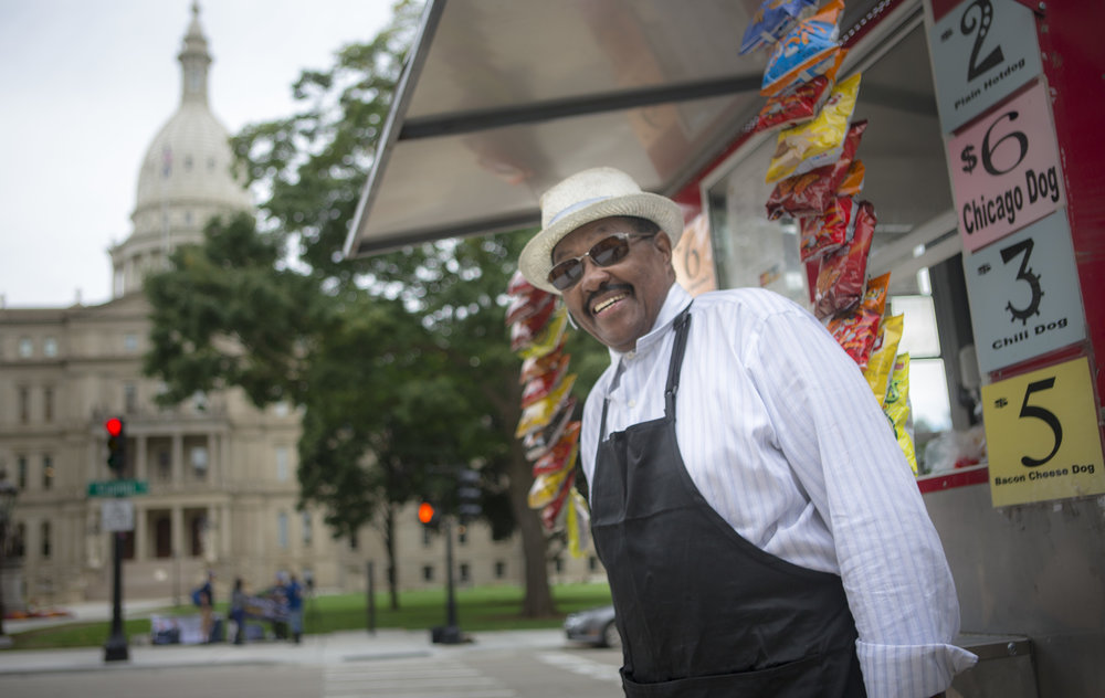 "CLINT, THE CATERER   //  Lansing, Michigan   ""Democrats, for the last 50 years, have been voting the same people in, and Black neighborhoods have stayed the same. Donald Trump is going to change that.""    ""Still a lot of crime on the south side,"" Clint says, ""but the downtown is better now than it was ten years ago.""  Clint's Hotdog Cart  – a mobile ""No-Hassle Casual Catering"" business – is parked across the street from the Capitol building in Lansing, Michigan.  Also the Deacon at Mount Zion All Nations Bible Church, Clint says he plans to  ""pray a lot""  if Hillary Clinton wins. He's dismayed by how President Obama has  ""bowed down   in the Middle East""  and raises concerns about illegal immigration and the unfortunate status quo running the country.  ""If Hillary wins, it's going to be the same old stuff.""   Trump  ""doesn't seem like a racist to me, a little radical, but why don't we give him a chance? I know he's not going to be our savior, because we only got one savior.""    Lansing, MI: • City Population: 114, 297 (Metro Area: 534,684). • Per capita income: $18,298. • 56.5% white, 19.0% Black, 12.4% Latino, two or more races 7.7%, Asian 3.9%. • Percentage below poverty line: 37.7%."