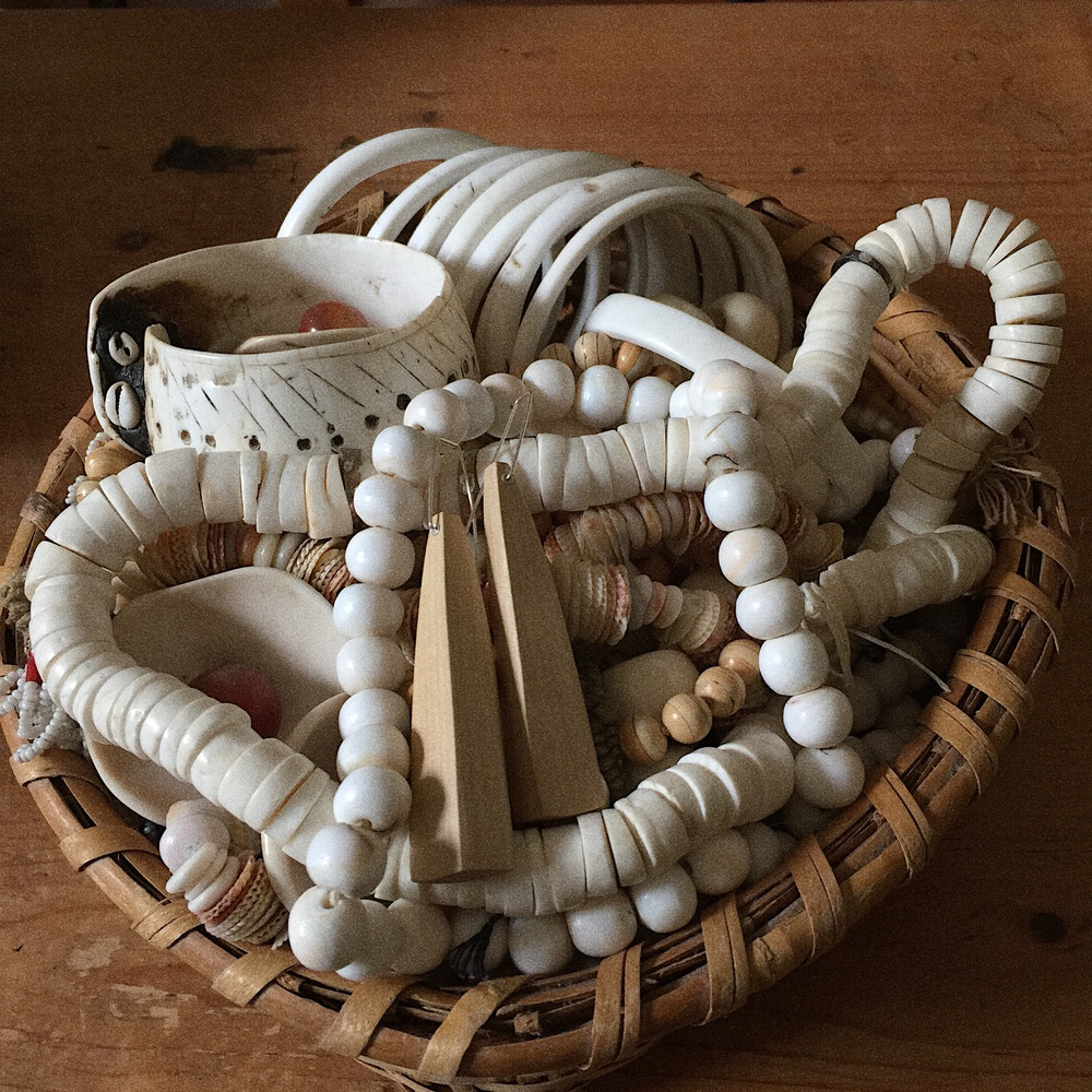 A basket of my own jewelry, collected over a lifetime, much of it antique. In the forefront a pair of my pearwood earrings to show how well they work with all the neutrals. My earrings are hand carved and sculpted, not simply cut from lumber and finished. Many shapes are one of a kind.