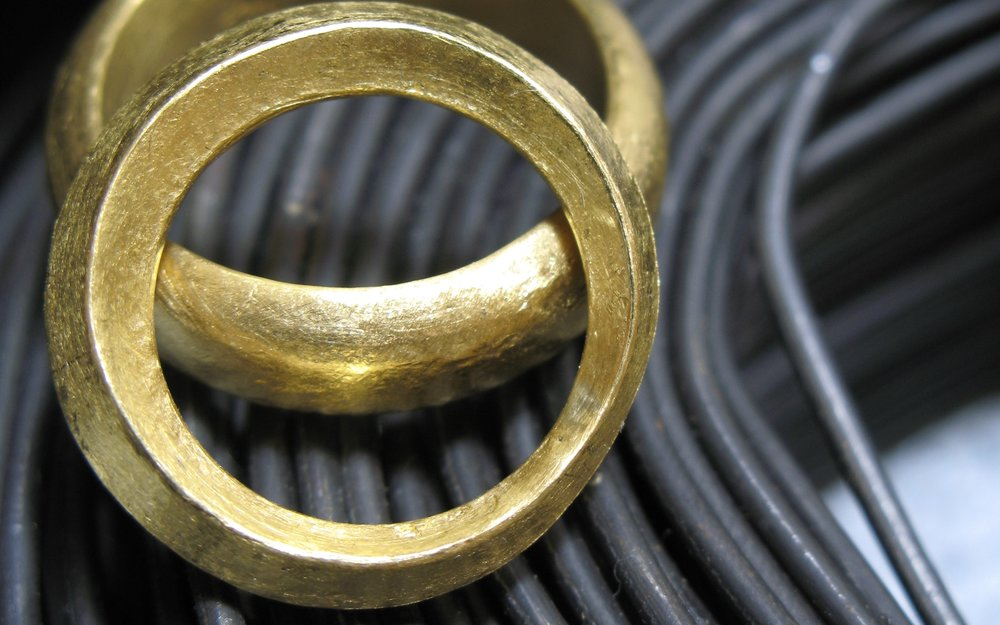 a handsome pair of wedding rings, hand forged in 24k gold
