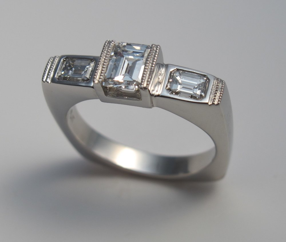 The design of this platinum ring began with the bride's mother's central emerald cut diamond. I carved the design in wax and the stones were set and detailed with milgrain.