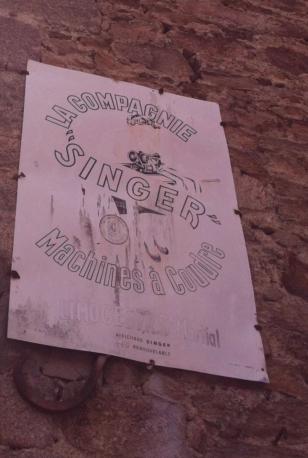 vintage faded singer advertisement in limoges, france.