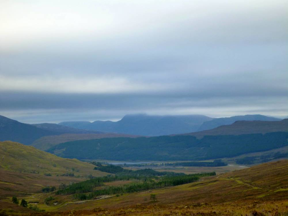 From Coulin Pass down to Loch Coulin, Beinn Eigh swathed in cloud in the background. The day's route descends to Coulin, crosses right to the forest, climbs through the forest, emerging at the notch, and passes under the craig on the hill behind before dropping down to Kinlochewe.