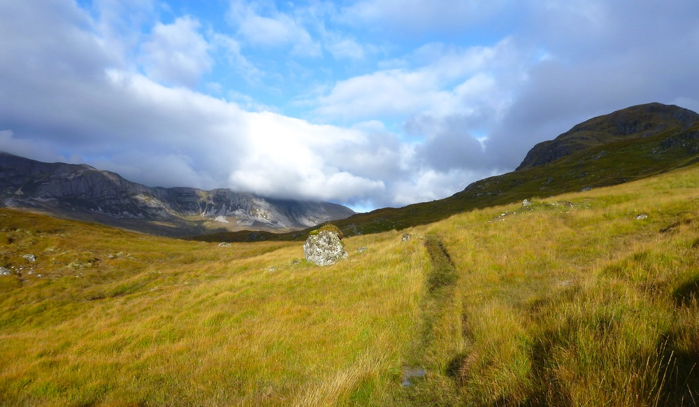 The old stalkers' path along the grassy slopes of upper Glen Oykel. The bealach we are heading for lies to the right of the cliffs of Braebag, which close in from the left in the distance.