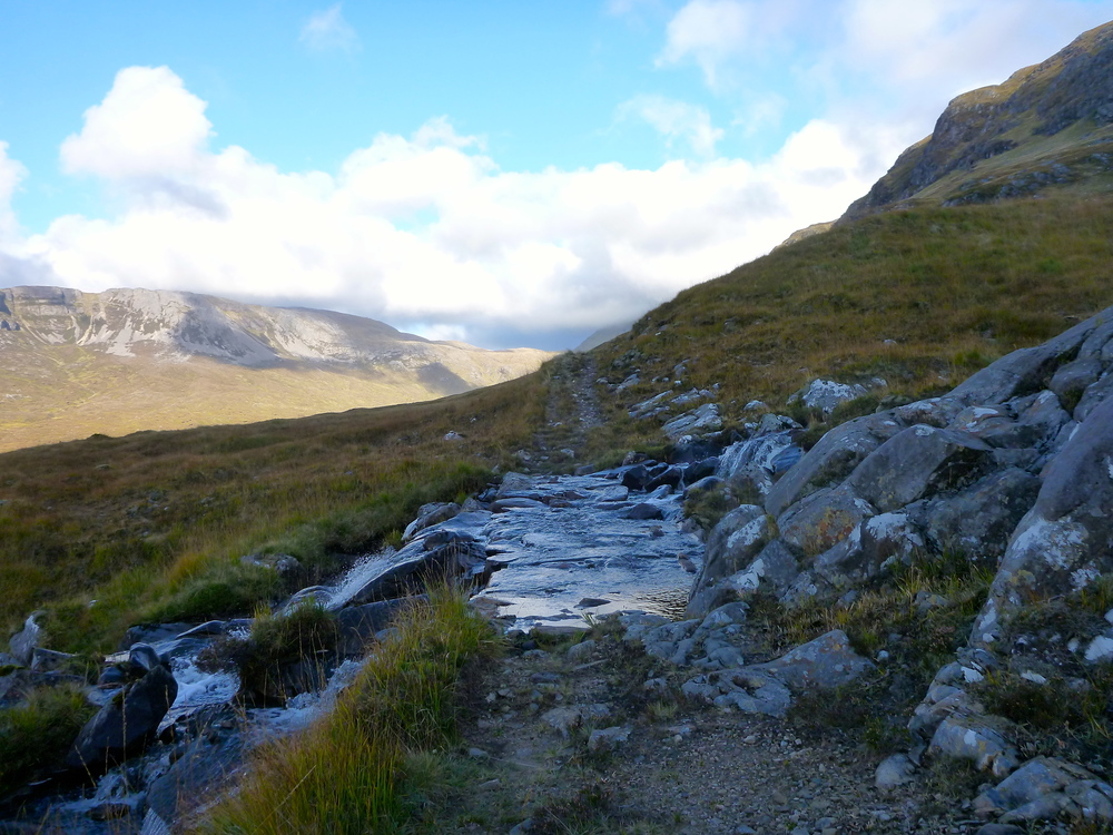 A beautifully-built ford over the vigorous stream from Dubh Loch Beag: this carefully interlocked paving has stood a hundred years or more. Braebag is in the sunshine on the left, and the shoulder of Conival can just be seen rising into the cloud in the centre.