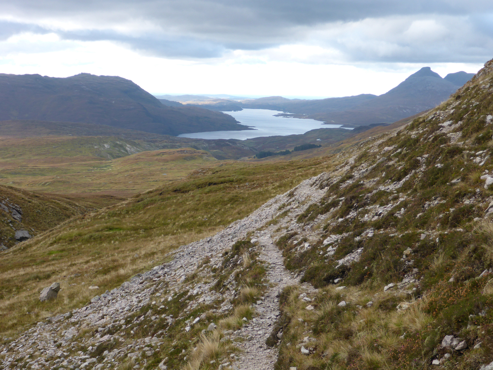 First view over the bealach and down to a whole new landscape: Loch Assynt, with Quinag soaring on the right. Inchnadamph lies at the lochside just out of view. The defile of Allt a' Bhealaich is to the left.