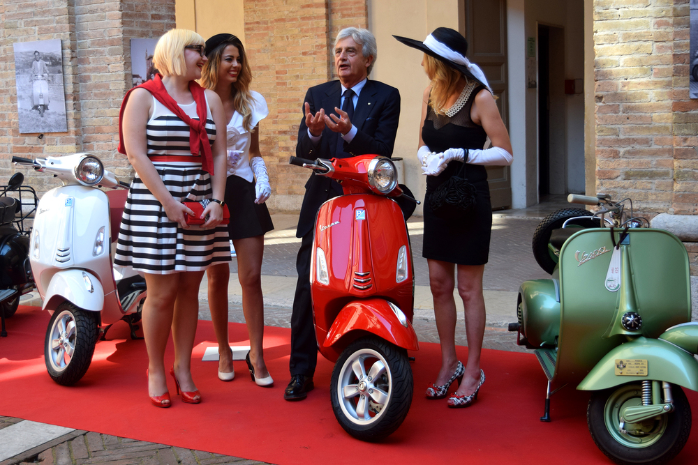 Guests of honor (from left) Chiara De Leone, Bianconi Chiara and Axontii Liudmile Gualie (right) talk with Riccardo Costagliola, the president of the Piaggio Foundation, at the Vespa exhibition show in Urbino, Italy, in June 2015. Photo by: Ryan Young/IEI Media - The Urbino Project.