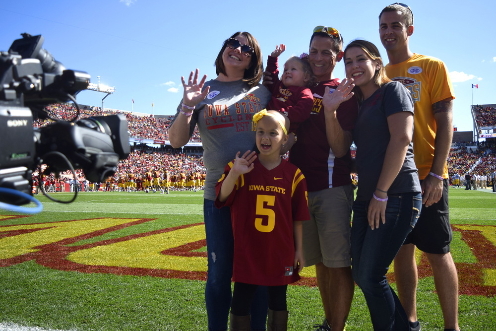 Maddy Snow waves at the camera while filming a video segment with her family before the 2015 CyHawk football game at Jack Trice Stadium in Ames, Iowa. Photo by: Ryan Young/Iowa State Daily.