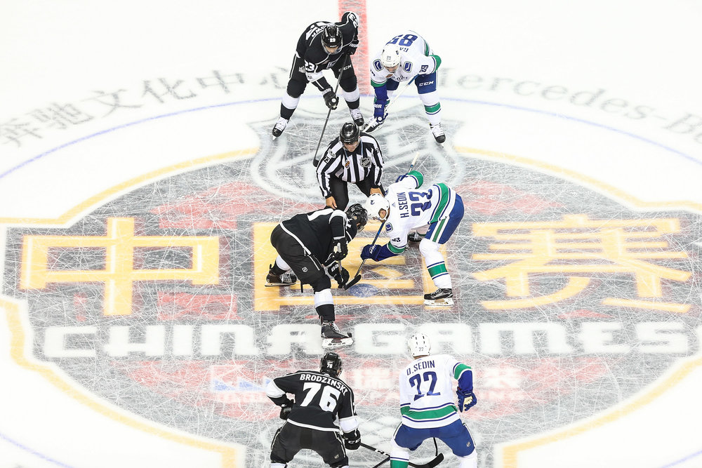 Players faceoff during a pre-season NHL game between Vancouver and Los Angeles at Mercedes-Benz Arena on September 21, 2017, in Shanghai. (Yifan Ding/Getty Images)