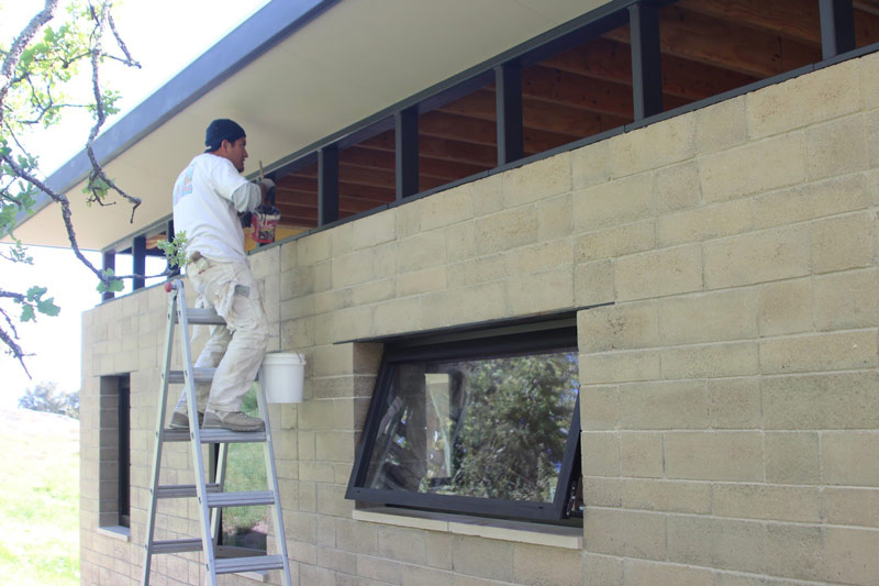 Mauricio painting the clerestory truss frames