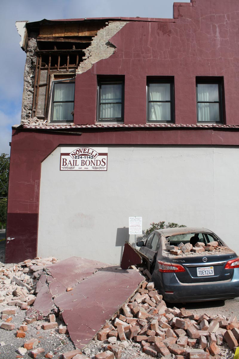 A car damaged by a 6.0-magnitude earthquake sits outside a bail bonds business in Napa, California. (August 24, 2014).  Image credit Matthew Keys, used with permissions of Creative Commons Attribution No Derivatives 2.0 license.