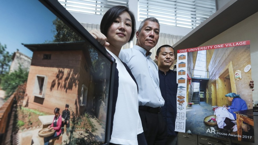 "Professor Edward Ng and colleagues Wan Li and Chi Xinan display a photo of a home they built from clay designed to withstand a magnitude 9 earthquake. ""we tried to think of ways we could use what was already existing to rebuild."""